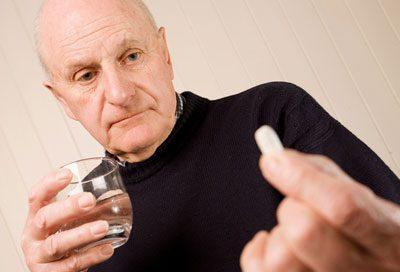 Пожилой человек с таблеткой
