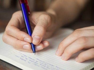 Человек пишет в тетрадь